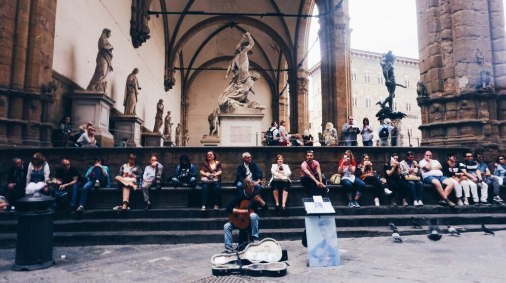 The photo of the musician and tourists sitting in front of the Loggia dej Lanzi